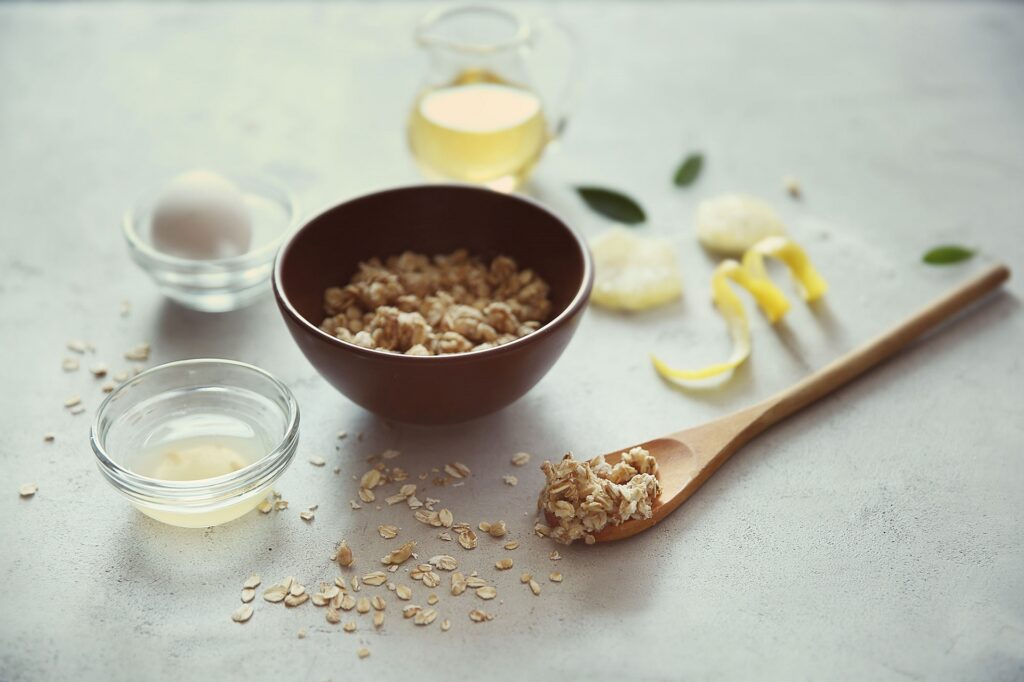 Natural scrub of oatmeal, olive oil and lemon on light background