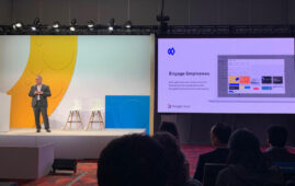 Photo of Google staff (standing on stage, left) with presentation slide of Currents with