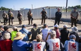 Law enforcement agents form a line in front of a wall of protesters who sit just in front of a locked gate at an Enbridge pump station, Monday, June 7, 2021, in Hubbard County, Minn. Indigenous protesters and allies occupied the active site, some physically chaining themselves to equipment, forcing workers to leave, in protest of the construction of Enbridge Line 3. (Alex Kormann/Star Tribune via AP)