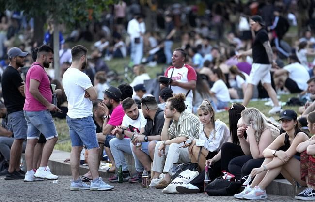 "People are seen at the ""Monbijoupark"" (Monbijou Park) during a warm summer evening in Berlin, Germany, Friday, June 11, 2021. (AP Photo/Michael Sohn)"