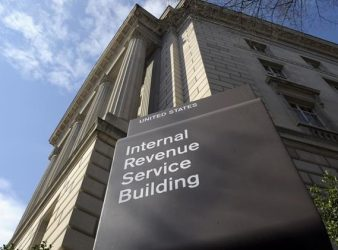 """FILE - In this March 22, 2013, file photo, the exterior of the Internal Revenue Service (IRS) building is seen in Washington. On Friday, Oct. 15, The Associated Press reported on stories circulating online incorrectly claiming a new tax policy allows the IRS to """"monitor all transactions involving bank accounts worth more than $600."""" (AP Photo/Susan Walsh, File)"""